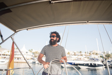 Positive bearded adult male in sunglasses floating on expensive boat on sea near port in sunny day