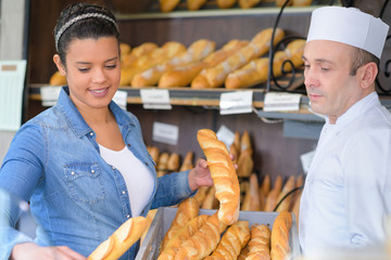 man and woman selling fresh loaves in bakery