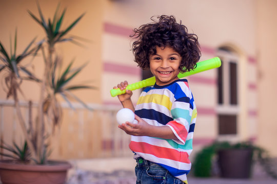 Happy kid with toy baseball equipment outdoor