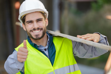 happy apprentice carrying wood on construction site