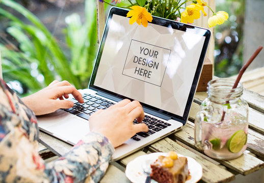 Laptop User Sitting at Table with Flowers and Food Mockup