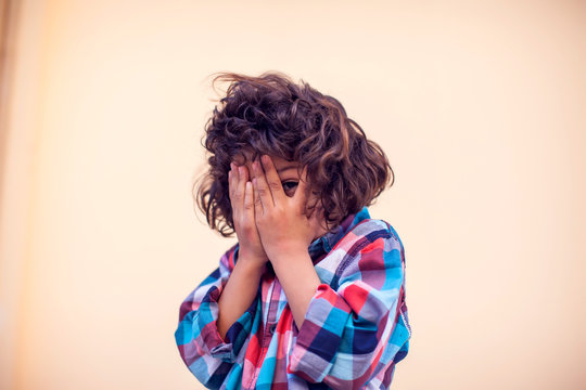 Closeup portrait shy little kid with curly hair