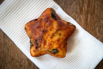 Homemade healthy freshly baked cornbread pastry in shape of star with cheese and spinach on wooden table