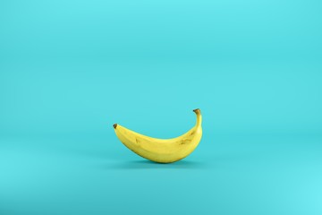 Single ripe yellow banana isolated on blue background. Minimal fruit idea concept.