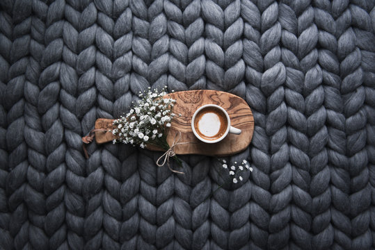 Directly above view of cup of cafe latte and flowers on wooden board