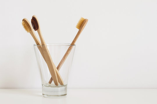set of natural toothbrushes in glass on table in bathroom