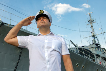 avy officer standing beside warship and do salute.The captain in white uniform stands under a battleship and saluting.