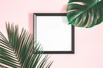 Summer composition. Tropical palm leaves, black photo frame on pastel pink background. Summer, nature concept. Flat lay, top view, copy space
