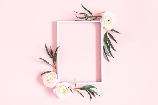 Flowers composition. White flowers, eucalyptus leaves, photo frame on pastel pink background. Flat lay, top view, copy space