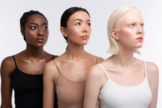 Three women with different skin color wearing camisoles