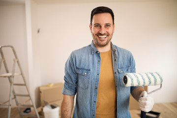 Young man painting apartment.