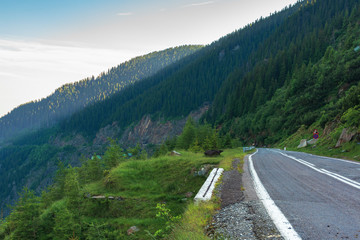 transfagarasan road at sunrise. popular travel destination of romania. beautiful summer landscape in mountains. road winding through gorge with steep rocky cliffs