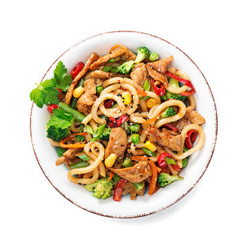 Udon stir fry noodles with pork meat and vegetables in a white plate isolated on white  background.