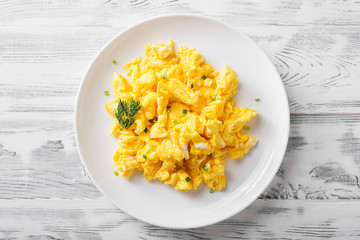 Scrambled eggs on white plate over white wooden background.