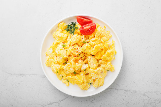 Scrambled eggs on plate over gray stone background.