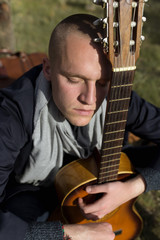 Young man resting with his guitar sitting on the grass in a sunny day