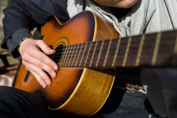 Detail of hands playing spanish guitar in a sunny day