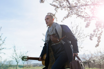 View through flowers of almond trees of young man with an old suitcase and guitar and trench coat is running