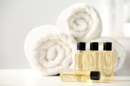 Mini bottles with cosmetic products and towels on table, space for text. Hotel amenities