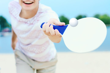 Young smiling man in light clothes is kicking ball with white matkot racket in hand. Cheerful male is playing in tennis and having fun on beautiful beach on nature. Summer activities concept. Wall mural
