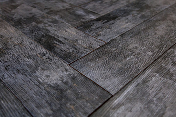 Modern vinyl floor with old wood imitation. Close-up of new gray flooring with texture from tiles with brown grains and knots. Decorative background of wooden boards.