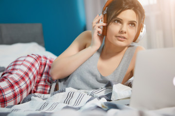 A Woman Using A Laptop And Listening To Headphones, While Lying On A Bed And Looking Up While