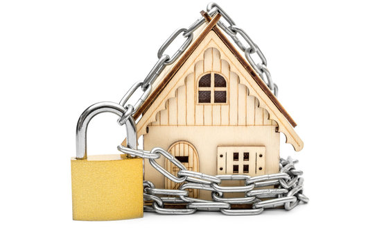 Model of house locked by padlock with chain. Isolated on white.
