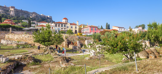 Fototapete - Library of Hadrian overlooking Acropolis and beautiful houses at Plaka district, Athens, Greece. It is a famous landmark of Athens. Panoramic scenic view of Ancient Greek ruins in the Athens center.