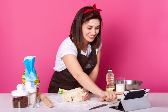 Portrait of happy smiling woman looks at tablet while kneading dough, prepares homemade pastry, baking Easter cake and hot cross bun, has video call with friend, being in good mood, wears casually.