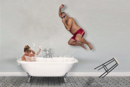 marito si tuffa nella vasca mentre la moglie si rilassa facendo un bagno caldo