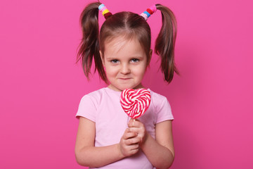 Beautiful fair haired child stands straight, looks directly at camera, holds colourful lollipop in hands, having frowny face, has no desire to share candy with anybody. Copy space for advertisement.