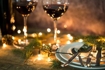 Closeup of red wine on table with Christmas lights. Christmas table and tree.