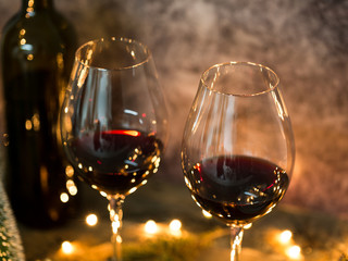 Red wine on table with Christmas lights on the background