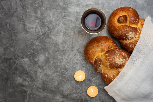 Shabbat Shalom - challah bread, shabbat wine and candles on grey background. Top view. With copy space
