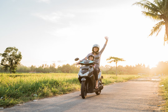 mom and her child enjoy riding motorcycle scooter in country ride road