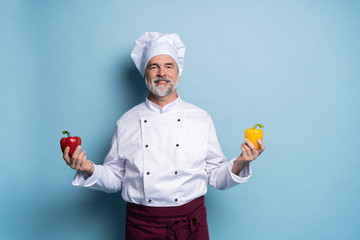 Food service, organic food, healthy diet, cooking and professional culinary concept - chef in white uniform holds vegetables.