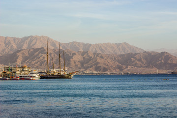 Poster Voile yacht city harbor south scenic landscape with different ships on water and desert rocky mountain ridge background