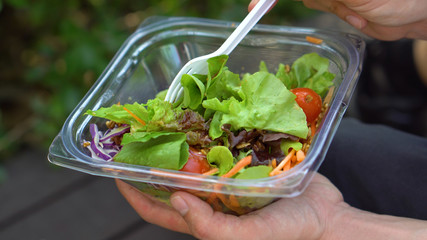 Mixing Delicious Healthy Salad in Take Away Plastic Container and Then Eating it