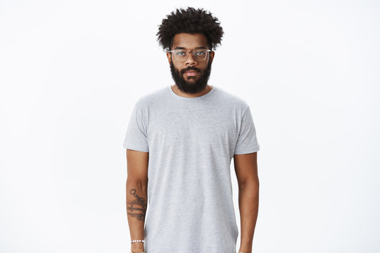Studio shot of masuline african american male with curly hair and beard wearing nose earring and glasses looking at camera with calm casual expression in ordinary pose over gray background