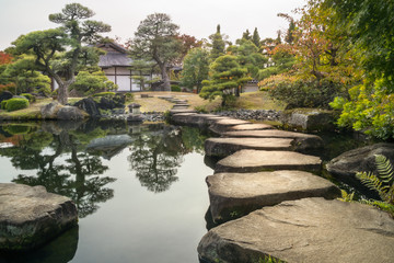 Perspective with large flat rocks forming a path over the pond and with a stone lantern and a Japanese building in the background, in autumn, at Koko-en Garden in Himeji, an Edo Style Japanese Garden