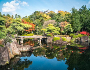 Small stone bridge over the pond full of koi fish at Koko-en Garden in autumn, with the rooftop of Himeji Castle just peeking over the tree line, in Japan.