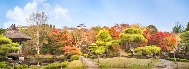Chinese style garden panorama in autumn at Koko-en Japanese Gardens with small stone bridges over the creek and with the rooftop of Himeji Castle just peeking over the colorful tree line.
