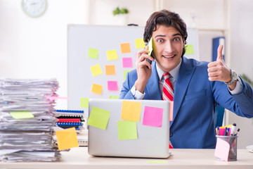 Young male handsome employee in conflicting priorities concept
