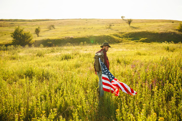 4th of July. Fourth of July. American with the national flag. American Flag. Independence Day. Patriotic holiday. The man is wearing a hat, a backpack, a shirt and jeans. Beautiful sunset light.  Wall mural