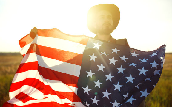 4th of July. Fourth of July. American with the national flag. American Flag. Independence Day. Patriotic holiday. The man is wearing a hat, a backpack, a shirt and jeans. Beautiful sunset light.