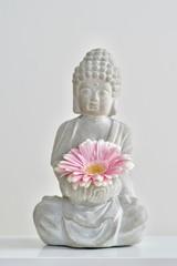 grey buddha sculpture holding pink gerbera daisy in praying hand