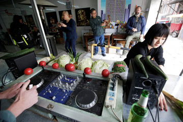 A DJ performs next to partygoers during a party at a vegetable market in downtown Beijing