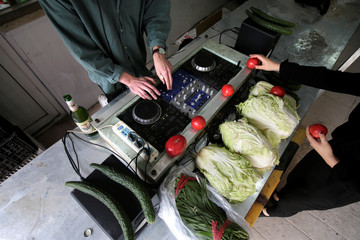 A DJ performs during a party at a vegetable market in downtown Beijing