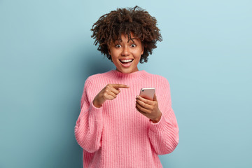 Surprised positive dark skinned lady points at smart phone device, suggests to have conversation in group chat, glad to recieve many messages of congratulation on mailbox, has overjoyed look
