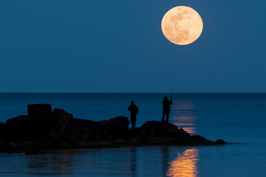 Two anglers are fishing in the Mediterranean and in the background the full moon rises and is reflected in the sea